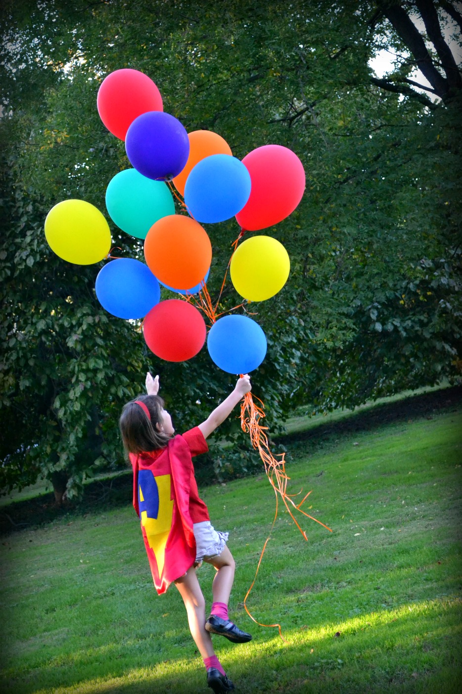 girl with a superhero cape on chasing ballons