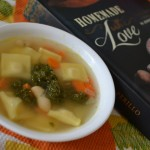 bowl of soup next to cook book